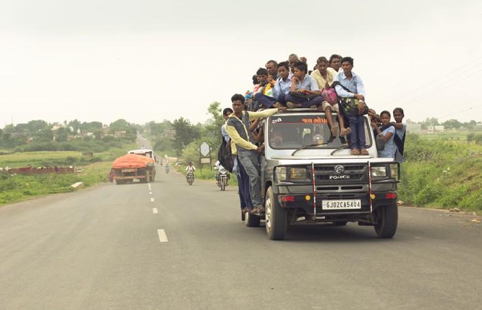 Lokálna preprava v Indii. Ľudia na streche auta.