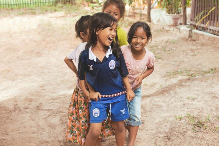 Smejúce sa deti v na školskom dvore. Kambodža na motorke Honda Win.