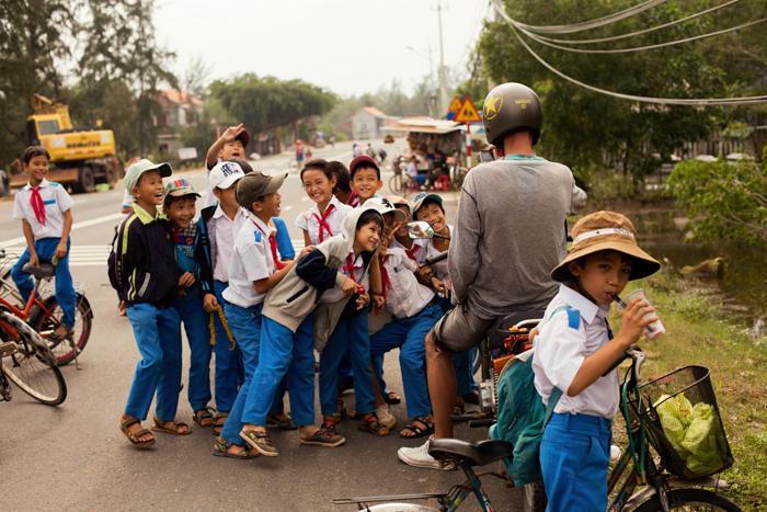 Množstvo deti vo Vietname na ceste s motorkárom.