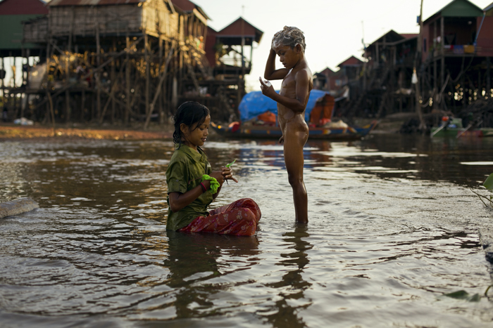Deti v Kambodži sa umývajú v jazere Tonle Sap, okolo domy na koloch. Kambodža na motorke Honda Win.
